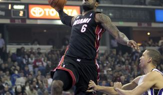 Miami Heat forward LeBron James, left, dunks over Sacramento Kings forward Francisco Garcia during the first quarter of an NBA basketball game in Sacramento, Calif., Saturday, Jan. 12, 2013. (AP Photo/Rich Pedroncelli)