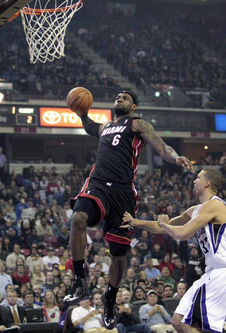 Miami Heat forward LeBron James, left, dunks over Sacramento Kings forward Francisco Garcia during the first quarter of an NBA basketball game in Sacramento, Calif., Saturday, Jan. 12, 2013. (AP Photo/Rich Pedroncelli)