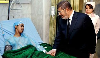 Egyptian President Mohammed Morsi (right) visits a victim receiving treatment at a military hospital in Cairo on Jan. 15, 2013, following a train crash in Badrasheen, 40 kilometers (25 miles) south of Cairo. At least 19 people died and more than 100 were injured when two railroad passenger cars derailed, health officials say. (Associated Press/Egyptian Presidency)