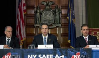 New York Gov. Andrew Cuomo (center) speaks during a news conference announcing an agreement with legislative leaders on New York's Secure Ammunition and Firearms Enforcement Act in the Red Room at the Capitol on Monday, Jan. 14, 2013, in Albany, N.Y. Also pictured are Secretary to the Governor Larry Schwartz (left) and Lt. Gov. Robert Duffy. (AP Photo/Mike Groll)
