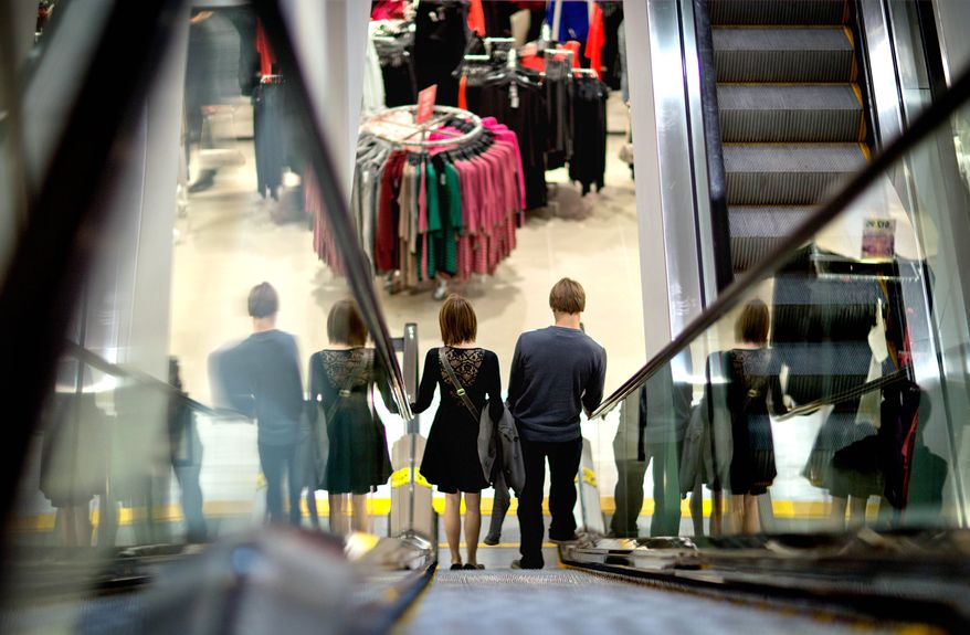 **FILE** A couple descend an escalator while shopping at an H&M store in Atlanta on Dec. 12, 2012. (Associated Press)