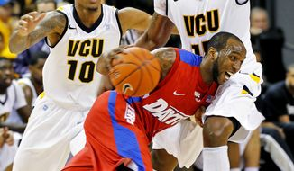 Dayton's Kevin Dillard (1) drives against Virginia Commonwealth's Darius Theus (10) and Juvonte Reddic (15) during the first half of their NCAA college basketball game, Wednesday, Jan. 9, 2013, in Richmond, Va. (AP Photo/Richmond Times-Dispatch, Mark Gormus)