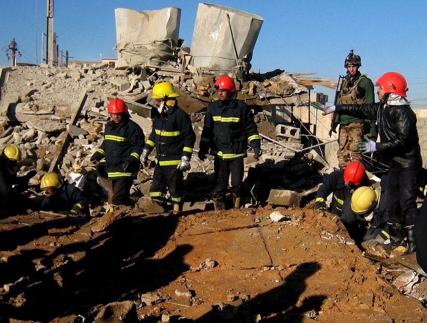 Firefighters look for survivors at the local headquarters of the Kurdistan Democratic Party after a bomb attack in Kirkuk, 180 miles (290 kilometers) north of Baghdad, Iraq, Wednesday, Jan. 16, 2013. (AP Photo/ Emad Matti)