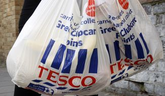 **FILE** A photo from April 21, 2009, shows Tesco shopping bags being carried in London. (Associated Press)