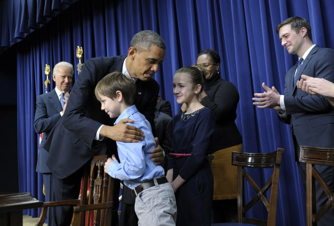 President Obama, accompanied by Vice President Joseph R. Biden (left), hugs 8-year-old letter writer Grant Fritz during a news conference on proposals to reduce gun violence on Wednesday, Jan. 16, 2013, in the South Court Auditorium at the White House complex in Washington. Mr. Obama and Mr. Biden were joined by law enforcement officials, lawmakers and children who wrote the president about gun violence following the shooting at an elementary school in Newtown, Conn., last month. (AP Photo/Susan Walsh)