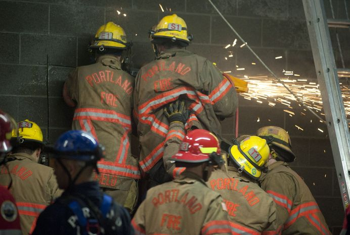 Firefighters work to free a woman who fell part of the way down a 20-foot wall and got stuck between two buildings in Portland, Ore., on Wednesday, Jan. 16, 2013. (AP Photo/The Oregonian, Brent Wojahn)