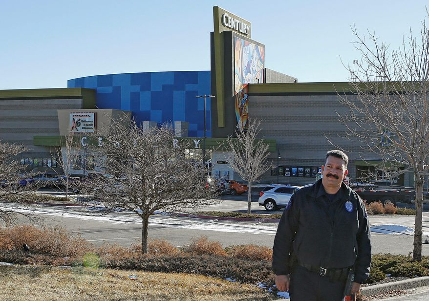 Officer Mike Moore guards the newly renamed Century Aurora movie theater Thursday in Aurora, Colo. Six months after a gunman killed 12 people and wounded 70, it reopens with a private ceremony for victims, first responders and officials. (Associated Press)