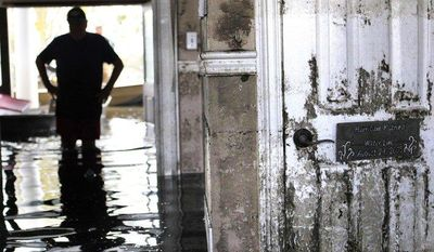 ** FILE ** In this Sept. 2, 2012, file photo, Don Duplantier walks through his flooded home as water recedes from Hurricane Isaac in Braithwaite, La. (AP Photo/Gerald Herbert, File)
