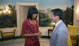 In this image released by the White House, first lady Michelle Obama greets David Hall, one of eight citizen co-chairs for the Inauguration, in the Diplomatic Reception Room of the White House in Washington on Jan. 17, 2013. (Associated Press/The White House, Lawrence Jackson)