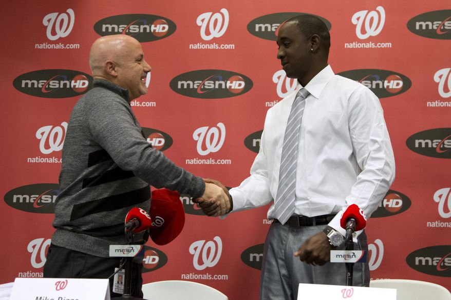Washington Nationals general manager Mike Rizzo, left, shakes hands with newly acquired pitcher Rafael Soriano during an introductory news conference at Nationals Park, Thursday, Jan. 17, 2013, in Washington. Rizzo also discussed the three-team trade that sent Michael Morse to the Seattle Mariners in exchange for pitching prospect A.J. Cole from the Oakland Athletics. (AP Photo/ Evan Vucci)