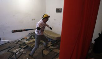 In this Dec. 27, 2012, photo visitor Savo Duvnjak smashes furniture and other household items during a demolishing session at the Rage Room, in Novi Sad, Serbia. (AP Photo/Darko Vojinovic)