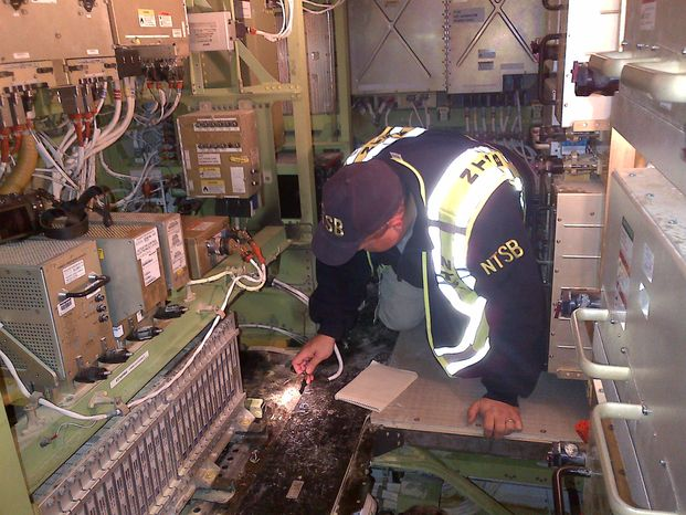 "In this image released by the National Transportation Safety Board and released Jan. 11, 2013, NTSB Investigator Mike Bauer works inside the Boeing 787 ""Dreamliner"" airplane under investigation at Boston's Logan Airport on Jan. 8. (Associated Press/NTSB)"