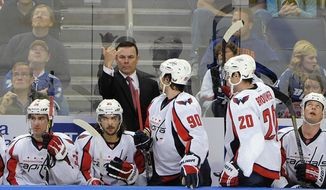 Washington Capitals coach Adam Oates, center, signals from the bench during the first period of the Capitals' NHL hockey game against the Tampa Bay Lightning on Saturday, Jan. 19, 2013, in Tampa, Fla. (AP Photo/Brian Blanco)