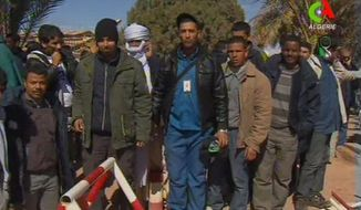 Unidentified rescued hostages pose for the media in Ain Amenas, Algeria, in this image taken from television Friday, Jan. 18, 2013. (AP Photo/Canal Algerie via Associated Press TV)