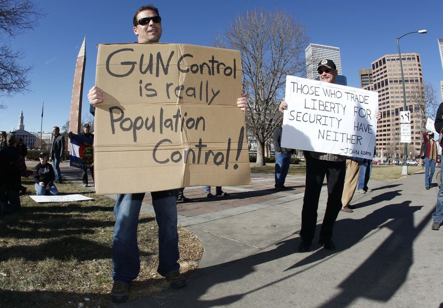 **FILE** Craig Larson (right) of Fort Collins, Colo., joins another protester who refused to identify himself in waving placards during a pro-gun rally in a park across from the Colorado Capitol in Denver on Jan. 9, 2013. (Associated Press)