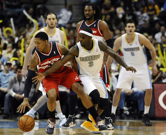 Denver Nuggets guard Ty Lawson, right, tries to steal the ball from Washington Wizards guard Bradley Beal, left, in the second half of an NBA basketball game between the Washington Wizards and the Denver Nuggets on Friday, Jan. 18, 2013, in Denver. The Wizards won 112-108. (AP Photo/Chris Schneider)