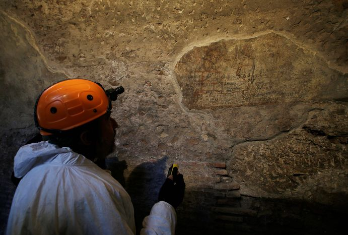 A restorer shows journalists an ancient graffiti recently discovered inside a gallery of Rome's Colosseum, Friday, Jan. 18, 2013. (AP Photo/Gregorio Borgia)