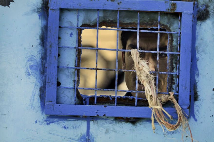 A prisoner looks out his cell window at the main prison in Kandahar, Afghanistan, in April 2011. (AP Photo/Allauddin Khan)