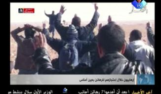 ** FILE ** A group of people believed to be hostages kneel in the sand with their hands in the air at an unknown location in Algeria in this image made from video. Algerian demining teams were scouring a gas refinery on Sunday, Jan. 20, 2013, that was the scene of a bloody four-day standoff, searching for explosive traps left by the Islamist militants who took dozens of foreigners hostage. (AP Photo/Ennahar TV)