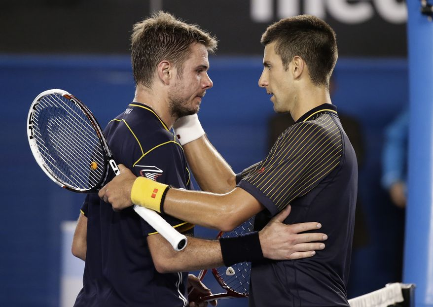 Serbia's Novak Djokovic, right, embraces Switzerland's Stanislas Wawrinka after winning their fourth round match at the Australian Open tennis championship in Melbourne, Australia, Monday, Jan. 21, 2013.(AP Photo/Andy Wong)