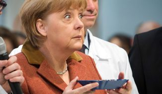 German Chancellor Angela Merkel looks up after smelling coffee beans during the opening tour of the International Green Week in Berlin on Friday, Jan. 18, 2013. (AP Photo/dpa, Michael Kappeler)