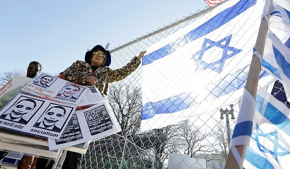 Protester Theresa Cao, of Washington, stands near the White House on Pennsylvania Avenue, Sunday, Jan. 20, 2013, in Washington. Thousands are expected to march during the 57th Presidential Inauguration parade after the ceremonial swearing-in of President Barack Obama on Monday. (AP Photo/Steve Helber)