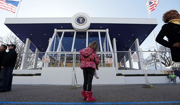 Evalina Lentini, of Ohio, looks at the Presidential viewing stand near the White House on Pennsylvania Avenue, Sunday, Jan. 20, 2013, in Washington. Thousands are expected to march during the 57th Presidential Inauguration parade after the ceremonial swearing-in of President Barack Obama on Monday. (AP Photo/Steve Helber)