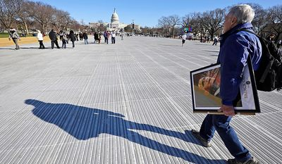 John Osler of Detroit, carries his artwork that is for sale, as he walks on the National Mall Sunday, Jan. 20, 2013, with the U.S. Capitol prepared for ceremonial swearing-in of President Barack Obama, the 57th Presidential Inaugural on Monday in Washington. (AP Photo/Alex Brandon)