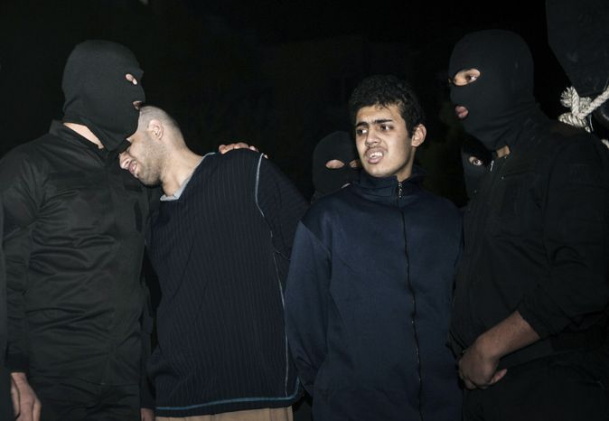 Alireza Mafiha (second from left) leans his head on the shoulder of a security officer moments before his execution along with Mohammad Ali Sarvari (second from right) in Tehran on Sunday, Jan. 20, 2013. Iran executed the two men publicly after a posting on YouTube in December showed the two men robbing and assaulting a man with a machete on a street in the Iranian capital. (AP Photo/ISNA, Amir Pourmand)