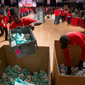 Zakki Scott of Washington, D.C., (left) and Charles Jordan of Laurel, with Stage Hands Union Local 22, join other volunteers loading supplies to be sorted into care packages for members of the armed services oversees and first responders during Saturday's National Day of Service at the D.C. Armory. (Andrew Harnik/The Washington Times)