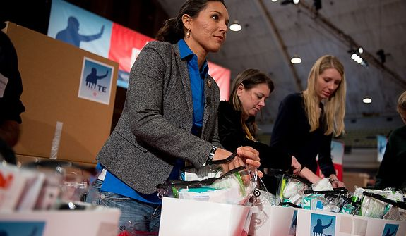 Rep. Tulsi Gabbard (D-Hawaii), center, volunteers her time to help put together service packages for members of the armed services abroad during the National Day of Service at the D.C. Armory, Washington, D.C., Saturday, January 19, 2013. Non-profit groups are running hundreds of service projects for the Martin Luther King Jr. weekend. (Andrew Harnik/The Washington Times)