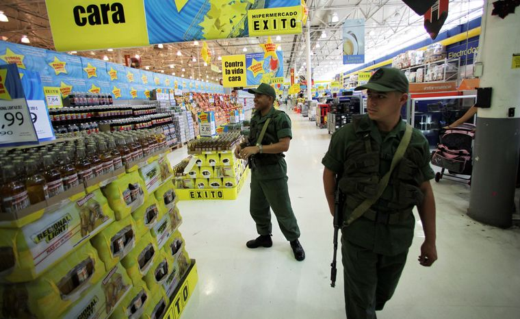 Venezuelan soldiers check prices at a supermarket in Caracas that the Chavez government has accused of raising costs. In a country riven by political strife, the military has been a unifying force. (Associated Press)
