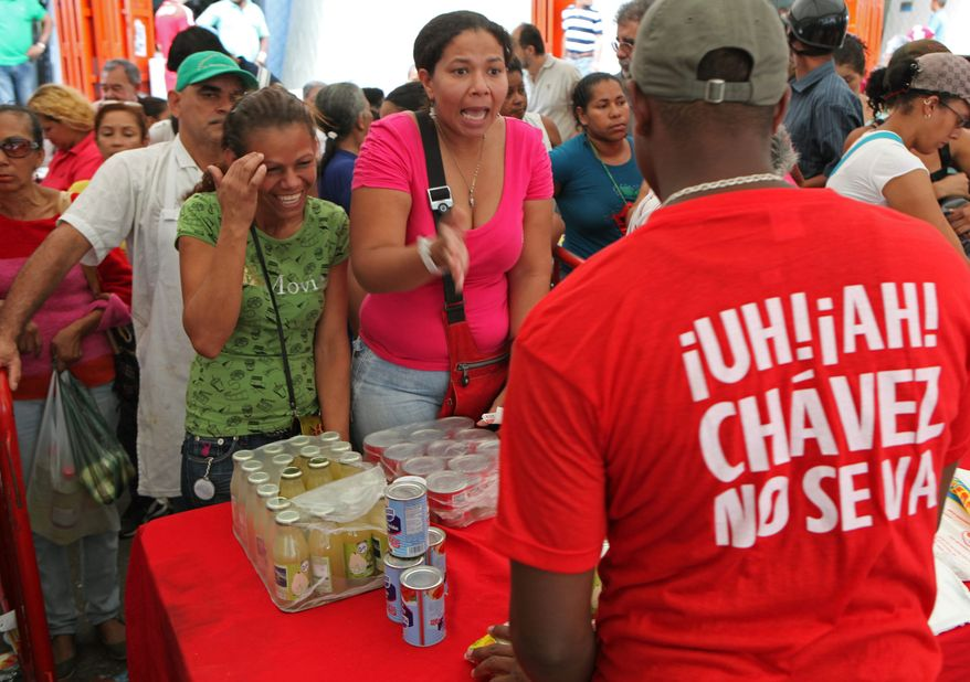 """Venezuelans swarm a government market in Caracas to buy subsidized food from a worker whose shirt translates as """"Oh no! Chavez isn't leaving."""" (Associated Press)"""