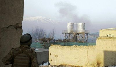 An Afghan security officer watches smoke rising from a rocket fired by militants that landed near the traffic police headquarters during an attack in Kabul, Afghanistan, on Monday, Jan. 21, 2013. (AP Photo/Musadeq Sadeq)