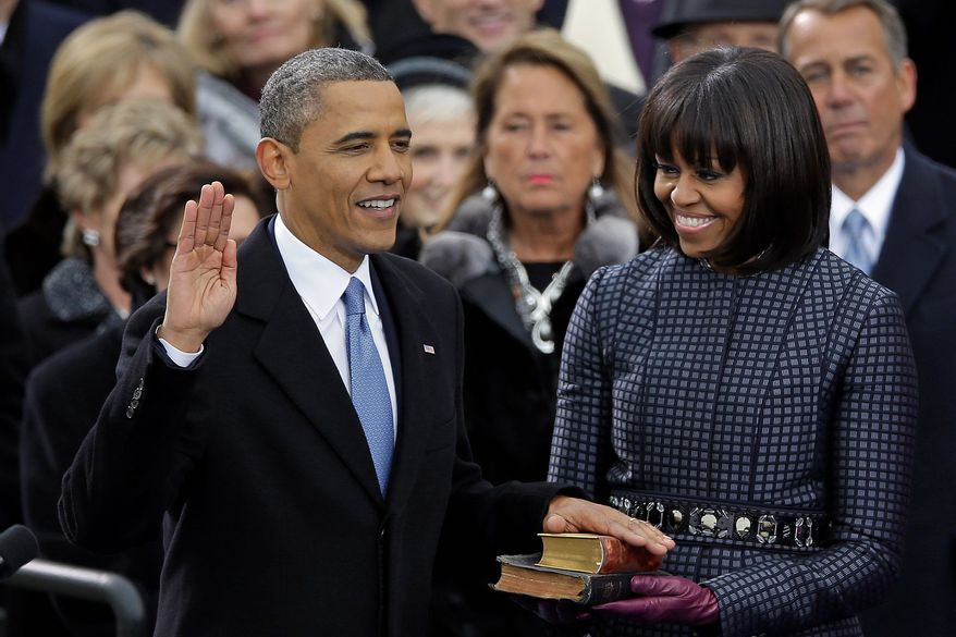 ** FILE ** First lady Michelle Obama was at her husband's side as he took the oath of office, holding the Bible as he pledged to protect and defend the Constitution. (Associated Press)