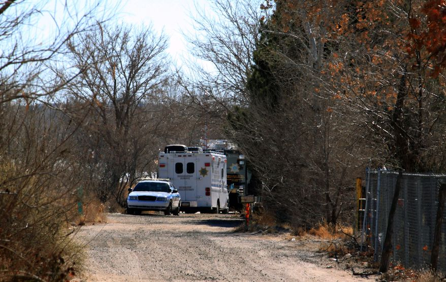 Bernalillo County authorities are stationed outside a home south of Albuquerque, N.M., on Sunday, Jan. 20, 2013, where two adults and three children were found shot to death. (AP Photo/Susan Montoya Bryan)