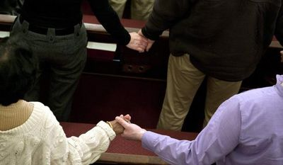"""Parishioners hold hands as they sing the song """"We Shall Overcome"""" at the end of an interfaith service at Newtown Congregational Church in Newtown, Conn., Sunday, Jan. 20, 2013. (AP Photo/Jessica Hill)"""