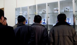 People look at 3G mobile phones in Pyongyang, North Korea, in December 2008. North Korea is loosening its restrictions on foreign cellphones and allowing visitors to bring their own phones into the country. The policy reverses a longstanding rule requiring visitors to relinquish their foreign phones at the border. (AP Photo/Xinhua News Agency, Zhang Binyang)