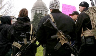 ** FILE ** Members of a Yakima, Wash., weapons seller carry firearms to a Second Amendment rally near the state Capitol in Olympia, Wash., on Saturday, Jan. 19, 2013. (Seattle Times via Associated Press)
