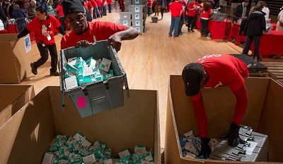 Zakki Scott of Washington, D.C., left, and Charles Jordan of Laurel, Md., right, with Stage Hands Union Local 22, load up supplies to be sorted into service packages for members of the armed services abroad by volunteers during the National Day of Service at the D.C. Armory, Washington, D.C., Saturday, January 19, 2013. Non-profit groups are running hundreds of service projects for the Martin Luther King Jr. weekend. (Andrew Harnik/The Washington Times)