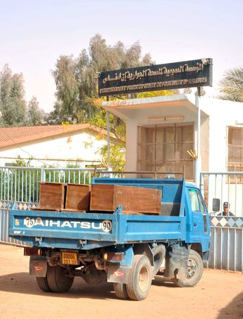 A truck loaded with empty coffins waits at the main entrance of the hospital where the bodies of persons killed during the hostage situation in a natural-gas plant are gathered in Ain Amenas, Algeria, on Monday, Jan. 21, 2013. (AP Photo/Anis Belghoul)