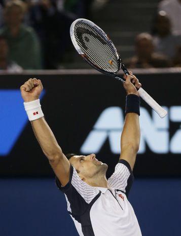 Serbia's Novak Djokovic celebrates his win over Tomas Berdych of the Czech Republic in their quarterfinal match at the Australian Open tennis championship in Melbourne, Australia, Tuesday, Jan. 22, 2013. (AP Photo/Dita Alangkara)