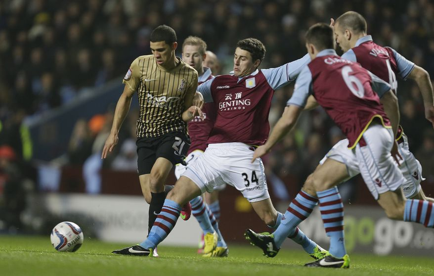 Aston Villa's Matthew Lowton, centre attempts to tackle Bradford City' Nahki Wells, left, during their English League Cup second leg semi-final soccer match at Villa's stadium in Birmingham, England, Tuesday, Jan. 22,2013.(AP Photo/Alastair Grant)