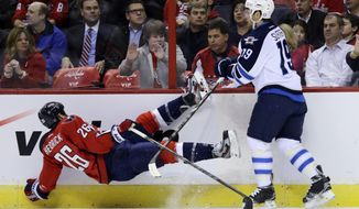 Washington Capitals center Matt Hendricks (26) falls to the ice after a check by Winnipeg Jets center Jim Slater (19) in the first period of an NHL hockey game on Tuesday, Jan. 22, 2013, in Washington. (AP Photo/Alex Brandon)