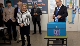 Israeli Prime Minister Benjamin Netanyahu casts his ballot accompanied by his wife, Sara, and their sons Yair and Avner in Jerusalem in Tuesday's parliamentary elections. (Associated Press)