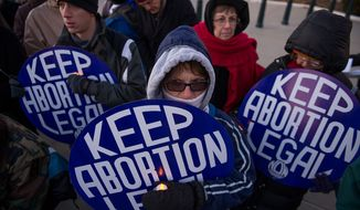Eric Wolfert (from left); Aileen, who did not give her last name; Norma Gattsek of Alexandria; and Linda Berg of Bethesda attend a National Organization for Women candlelight vigil to commemorate the 40th anniversary of Roe v. Wade, the Supreme Court decision that legalized abortion, in Washington on Tuesday, Jan. 22, 2013. (Andrew Harnik/The Washington Times)