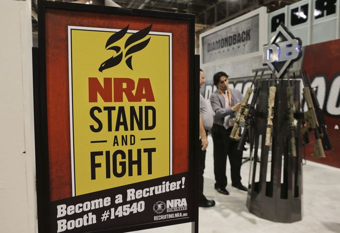**FILE** A Diamondback Firearms representative (rear right) explains features of one of their rifles on display at the 35th annual SHOT Show in Las Vegas on Jan. 16, 2013. (Associated Press)
