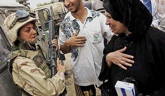 **FILE** An Iraqi woman greets U.S. Marine Sgt. Marykate Linnane in a Baghdad suburb on April 13, 2003. ( J.M. Eddins Jr./The Washington Times)