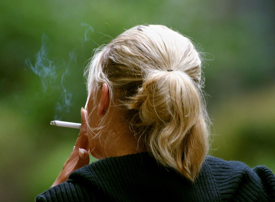 A woman smokes a cigarette during a break from work in downtown Chicago. (Associated Press)