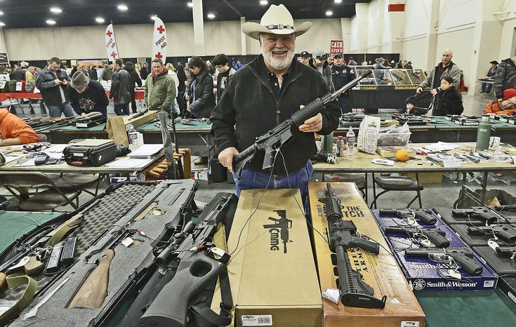 Ken Haiterman shows off a CMMG 5.56mm AR 15 at the 2013 Rocky Mountain Gun Show on Jan. 6 in Sandy, Utah. In spite of the recent school shootings in Newtown, Conn., gun enthusiasts flocked to the show to purchase weapons and ammunition. (Associated Press)
